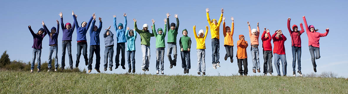 A line of kids jumping at the top of a hill