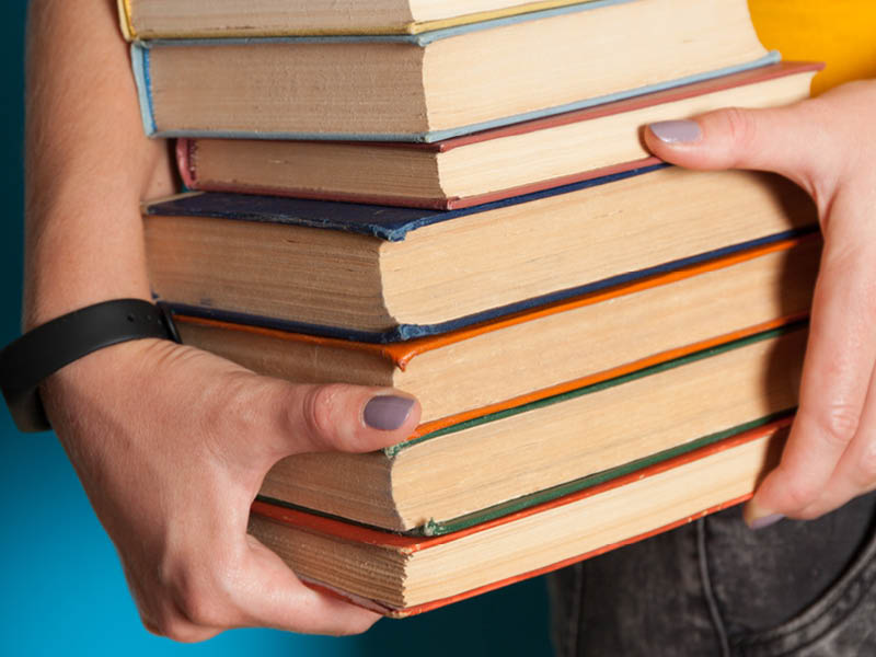 Hands carrying a pile of books